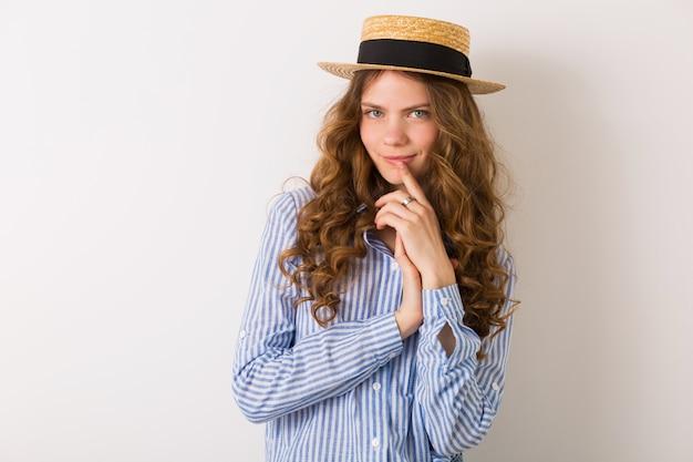 Портрет молодой красивой женщины с соломенной шляпой, джинсами, синей хлопковой рубашкой, позирует на белой стене