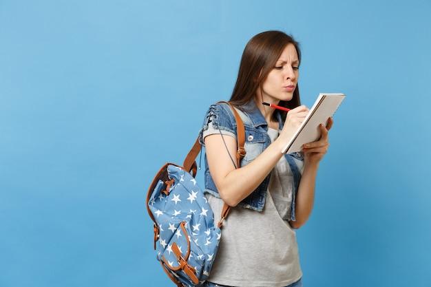 회색 티셔츠 데님 옷을 입은 어리둥절한 사려깊은 여학생의 초상화는 배낭을 메고 파란색 배경에 격리된 노트북에 필기를 하고 있습니다. 고등학교 대학 대학에서 교육.