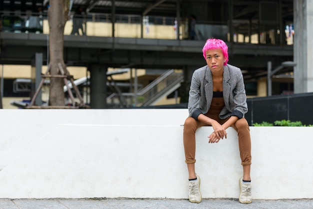 야외 도시 거리에서 분홍색 머리를 가진 젊은 반항적 인 아시아 사업가의 초상화