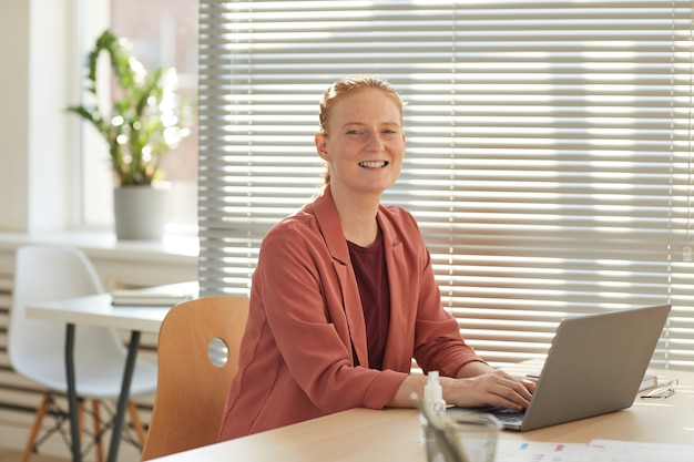 Портрет молодой рыжеволосой бизнес-леди, улыбаясь, используя ноутбук за столом в залитом солнцем офисе