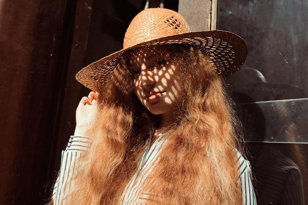 彼女の顔に影のある麦わら帽子の若い赤い髪のモデルの肖像画