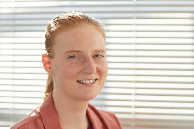 太陽に照らされたオフィスでブラインドにポーズをとって笑っている若い赤い髪の女性の肖像画
