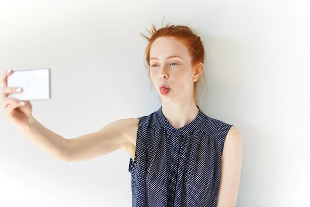 Selfie를 복용하는 젊은 빨간 머리 여자의 초상화