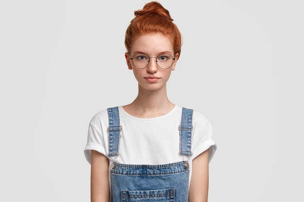 デニムのオーバーオールを着ている若い赤髪の女性の肖像画