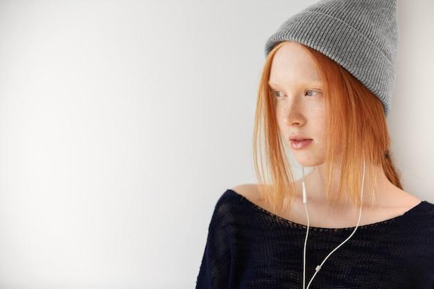 ヘッドフォンで若い赤髪の女性の肖像画