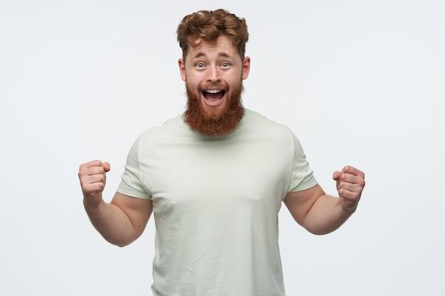 Портрет молодого рыжего бородатого мужчины носит пустую футболку, поднимает кулак и кричит во время просмотра футбольного матча.