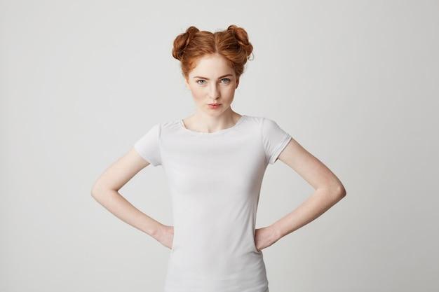 腕を腰に当てまっすぐに若い赤毛の女の子の肖像画。