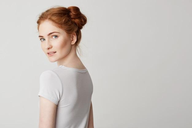 後ろを向いて立って、カメラを探しているパンと赤毛の若い女の子の肖像画。