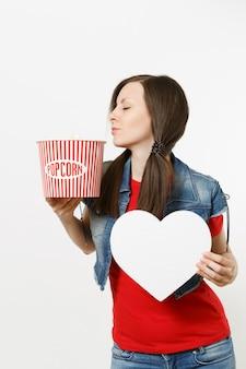 흰색 배경에 격리된 복사 공간이 있는 팝콘과 흰색 하트 양동이를 들고 영화를 보는 캐주얼한 옷을 입은 젊은 편안한 아름다운 여성의 초상화. 영화 개념의 감정.