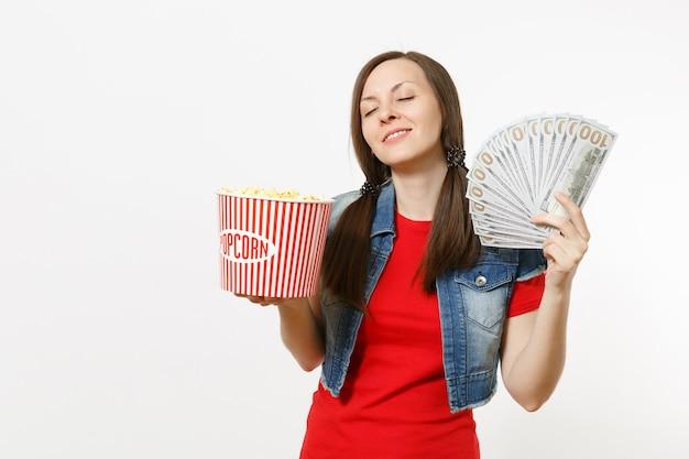 캐주얼 옷을 입고 영화를 보고, 팝콘 양동이와 달러 묶음, 흰색 배경에 격리된 현금 돈을 들고 눈을 감고 있는 편안한 젊은 여성의 초상화. 영화 속 감정.
