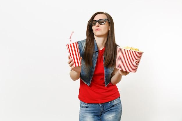 흰색 배경에 격리된 팝콘 양동이와 플라스틱 컵의 소다 또는 콜라를 들고 영화 영화를 보고 눈을 감고 3d 안경을 쓴 젊은 편안한 여성의 초상화. 영화 개념의 감정.