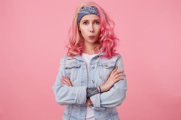 Портрет молодой грустной красивой розоволосой дамы в джинсовой куртке со скрещенными руками, недовольными взглядами, кто-то сказал ей что-то обидное, стоит.