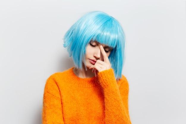 흰 벽에 파란 머리를 가진 젊은 슬픈 여자의 초상화. 주황색 스웨터를 입고.