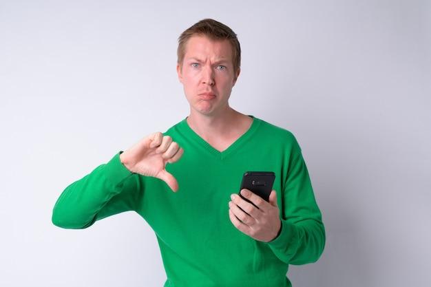 전화를 사용 하 고 아래로 엄지 손가락을주는 젊은 슬픈 남자의 초상화