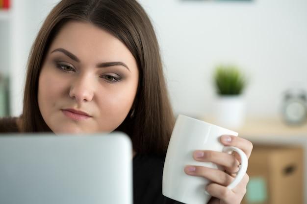ノートパソコンのモニターを見て、お茶の白い帽子を保持している若い悲しいまたは気配りのある女性の肖像画。オンライン教育、コーヒーブレイクまたはダイエットの概念