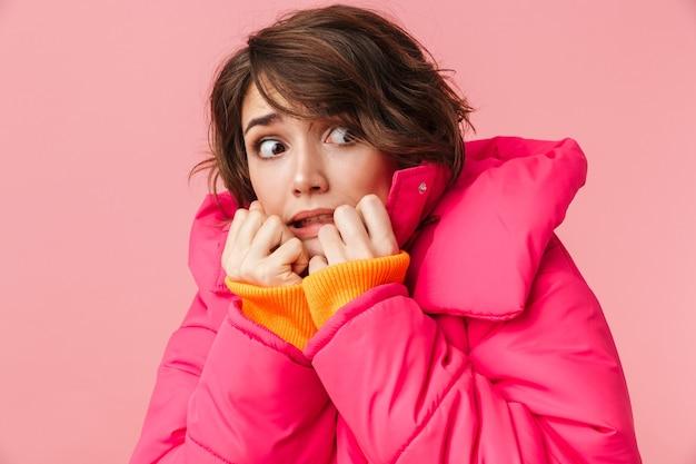 핑크색으로 격리된 채 따뜻한 코트를 입은 겁 먹은 젊은 여성의 초상화