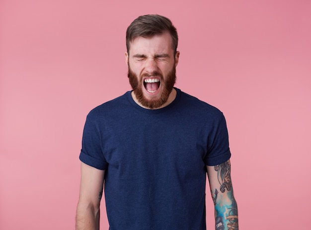 젊은 비명을 지르는 문신을 한 붉은 수염 난 남자의 빈 티셔츠에 강한 고통과 분노를 느끼고 닫힌 눈과 넓게 열린 입으로 분홍색 배경 위에 선다.