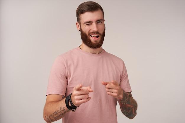 Портрет молодой самоуверенной брюнетки с бородой в бежевой футболке и модных аксессуарах, позирующей на белом, подмигивая и держа поднятыми указательные пальцы