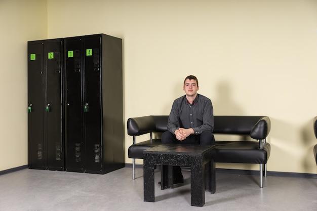 Портрет молодого серьезного делового человека, сидящего на кожаном диване перед маленьким столиком в раздевалке с четырьмя черными шкафчиками