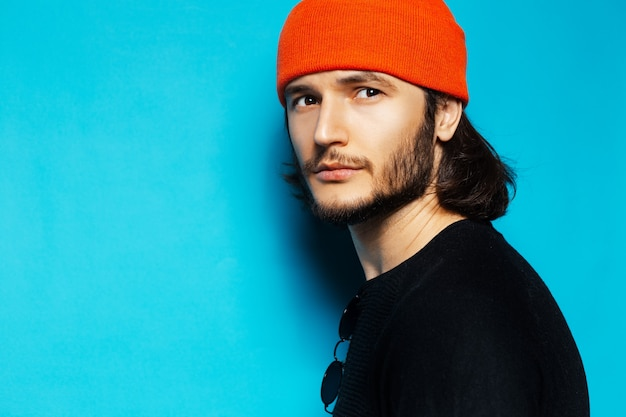 Портрет молодого серьезного парня в оранжевой шляпе на синем фоне.
