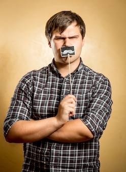 偽の口ひげを持つ深刻な若者の肖像