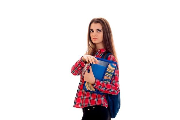 白い背景で隔離のノートブックのバックパックとフォルダーを持つ若い深刻な学生の女の子の肖像画