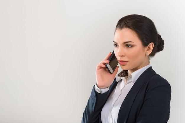 Портрет молодой серьезной женщины в деловой одежде разговаривает по телефону на сером фоне