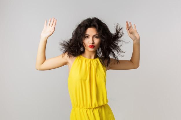 黄色のドレス、手を振っている巻き毛、夏のスタイル、ファッショントレンド、混合レース、分離、手を繋いでいる若いセクシーなブルネットの女性の肖像画
