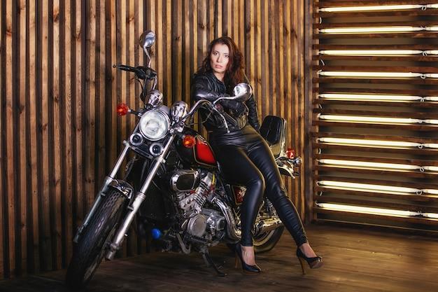 木製の壁の背景にスタジオでオートバイに座って、革のジャケットと革のズボンの若いセクシーなファッションブルネットの女性の肖像画