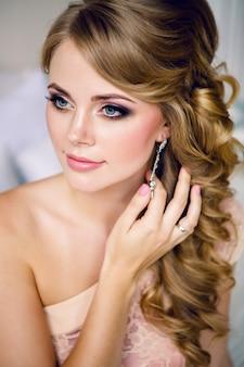 メイクアップのドレスで金髪の若いセクシーな女の子の肖像画