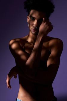 カジュアルなポーズで立っている影のトランスジェンダーモデルの若い上半身裸の運動選手の肖像画