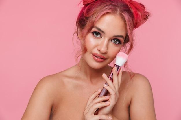 化粧ブラシで化粧品を適用するカラフルな髪型を持つ若い上半身裸の女性の肖像画