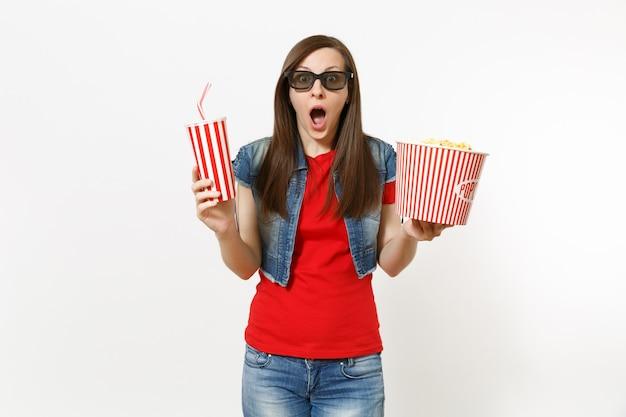 흰색 배경에 격리된 팝콘 양동이와 플라스틱 컵의 소다 또는 콜라를 들고 영화를 보고 있는 3d 아이맥스 안경을 쓴 젊은 충격을 받은 매력적인 여성의 초상화. 영화 개념의 감정.