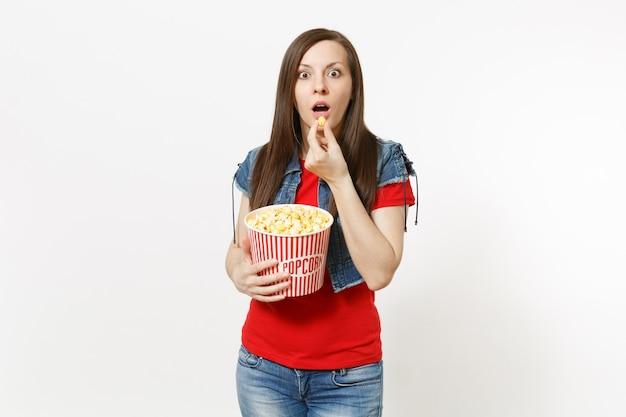 흰색 배경에 격리된 양동이에서 팝콘을 들고 먹는 공포 공포 영화 영화를 보고 있는 평상복을 입은 젊은 충격을 받은 아름다운 브루네트 여성의 초상화. 영화 개념의 감정.