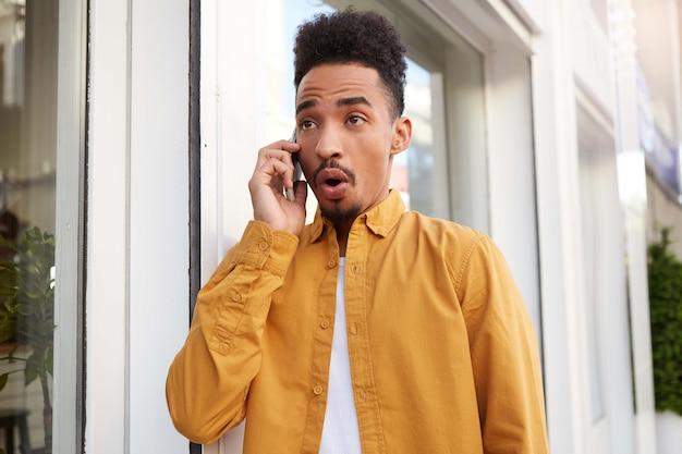 Портрет молодого шокированного смуглого мужчины в желтой рубашке, идущего по улице и разговаривающего по телефону со своими друзьями, слышит невероятные новости с широко открытыми глазами и ртом.
