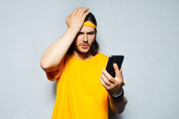 灰色の壁の背景に、黄色を着て、スマートフォンで見てショックを受けた若い男の肖像画。