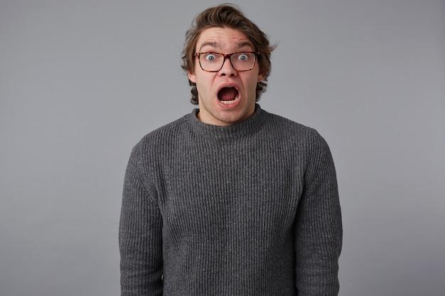 안경, 젊은 충격 된 남자의 초상화는 놀란 표정으로 넓은 오픈 입과 눈, 회색 배경 위에 서 무서워 보인다.