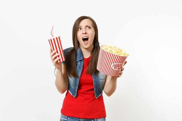 흰색 배경에 격리된 팝콘 양동이와 소다 또는 콜라 플라스틱 컵을 들고 평상복을 입고 영화를 보고 충격을 받은 젊은 여성의 초상화. 영화 속 감정.