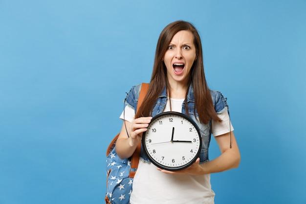 Портрет молодой шокированной раздраженной студентки с кричащим рюкзаком, держащим будильник, изолированный на синем фоне. время уходит. обучение в средней школе. скопируйте место для рекламы.