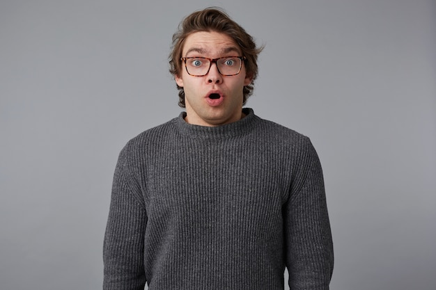 안경 충격을받은 젊은이의 초상은 입을 벌리고 눈을 가진 회색 스웨터를 입고, 놀란 표정으로 회색 배경 위에 서 있습니다.