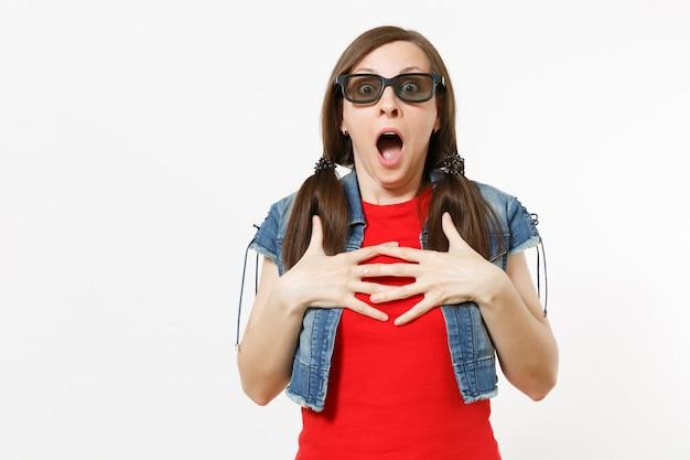 Портрет молодой шокированной испуганной женщины с открытым ртом в 3d-очках и повседневной одежде, смотрящей кинофильм, цепляясь за грудь, изолированную в студии на белом фоне. эмоции в концепции кино.