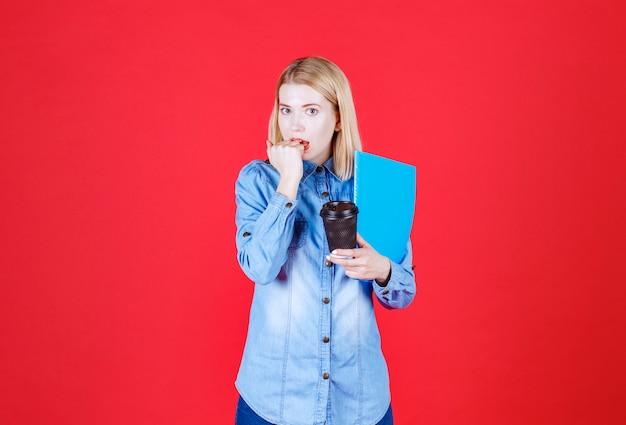 파란색 문서 폴더와 테이크 아웃 커피를 들고 그녀의 손을 물고 젊은 충격을받은 학생의 초상화