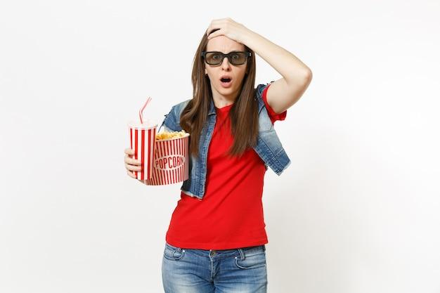 흰색 배경에 격리된 머리에 팝콘과 플라스틱 컵의 소다 또는 콜라를 들고 영화를 보고 있는 3d 안경을 쓴 충격을 받은 젊은 여성의 초상화. 영화 개념의 감정.