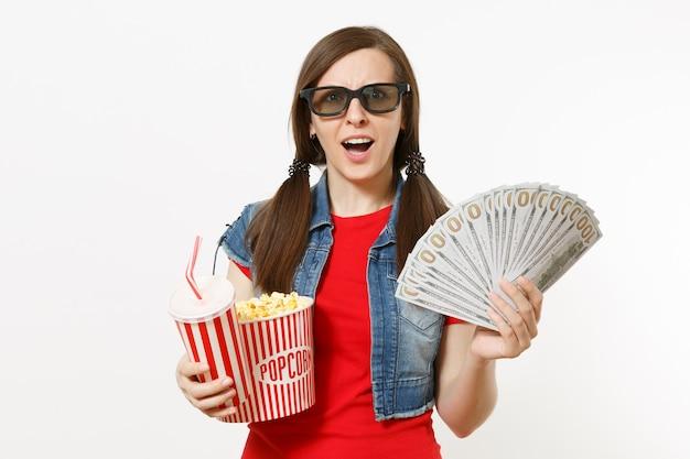 3d 안경을 쓰고 충격을 받은 젊은 여성의 초상화, 팝콘 양동이, 탄산음료 또는 콜라 한 컵, 달러 묶음, 흰색 배경에 격리된 현금. 영화 속 감정.