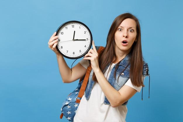 Портрет молодой потрясенной студентки в джинсовой одежде футболки с будильником удерживания рюкзака, изолированным на синем фоне. время уходит. обучение в университете. скопируйте место для рекламы.