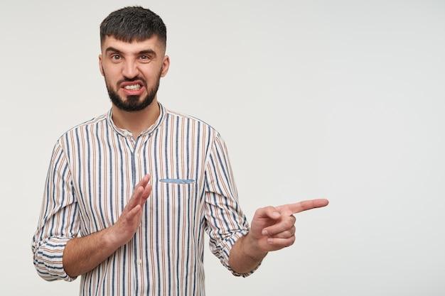 Портрет молодого бородатого брюнетки с короткими волосами в полосатой рубашке, который надул губы и морщился, показывая в сторону указательным пальцем, позируя над белой стеной