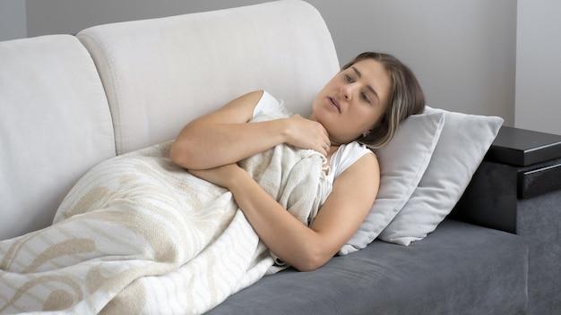 소파에 담요 아래에 누워 기분이 좋지 않은 젊은 아픈 여자의 초상화