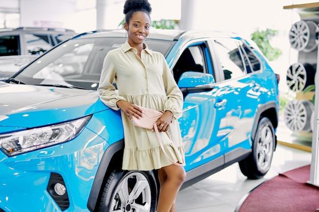 新しい青い車の横に立っている若いスリムなアフリカの女性の肖像画
