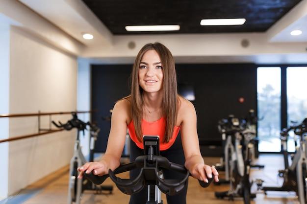 ジムでエアロバイクにスポーツウェアトレーニングでスリムな若い女性の肖像画。スポーツとウェルネスライフスタイルのコンセプト