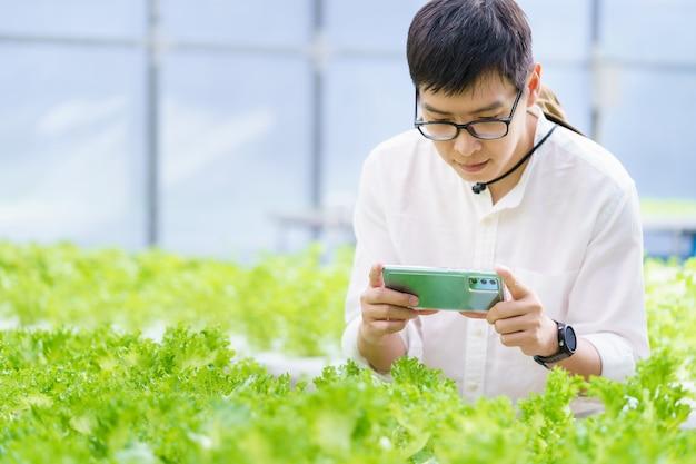 검사를 위해 디지털 태블릿 컴퓨터를 사용하는 젊은 스마트 농부의 초상화. 농업 재배 활동에서 농업 분야 응용 기술을 사용하고 품질 개념을 확인합니다.